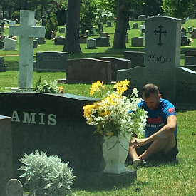 Photo of Farrel's husband, Zack, sitting in front of her dad's grave
