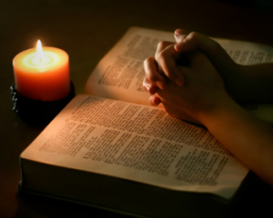 Photo of folded hands over a Bible, praying by candlelight. Used to illustrate the blog,